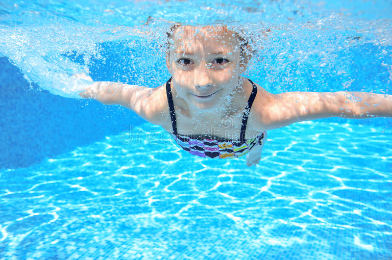 Het gelukkige actieve onderwaterkind zwemt in pool, het mooie gezonde meisje zwemmen stock foto's