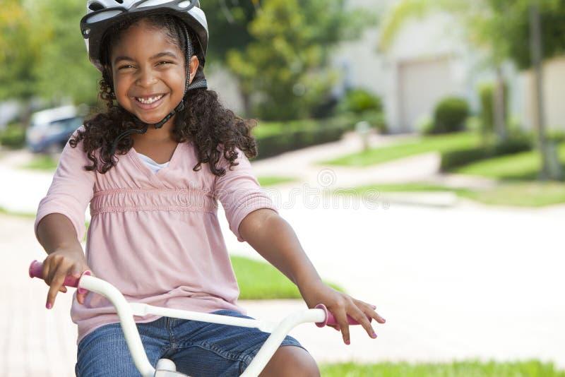 Het gelukkige Afrikaanse Amerikaanse het Berijden van het Meisje Glimlachen van de Fiets royalty-vrije stock foto