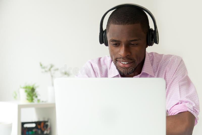 Het gelukkige Afrikaanse Amerikaanse letten op webinar bij laptop in bureau royalty-vrije stock fotografie
