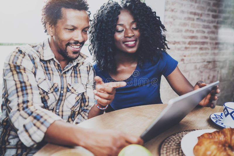 Het gelukkige Afrikaanse Amerikaanse paar heeft samen ontbijt in de ochtend bij de houten lijst Glimlachende zwarte mens en van h stock afbeelding