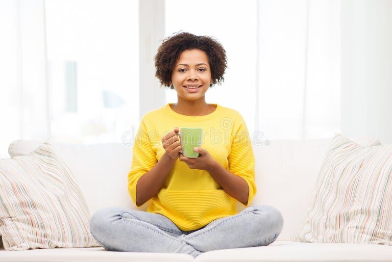Het gelukkige Afrikaanse Amerikaanse vrouw drinken van theekop stock fotografie