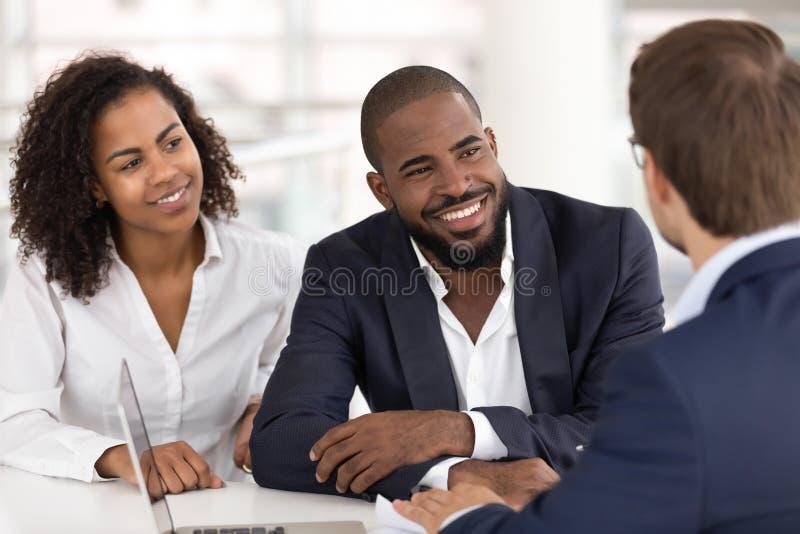 Het gelukkige Afrikaanse familiepaar luistert de raadplegende cliënten van de makelaar in onroerend goedverzekeraar stock foto's