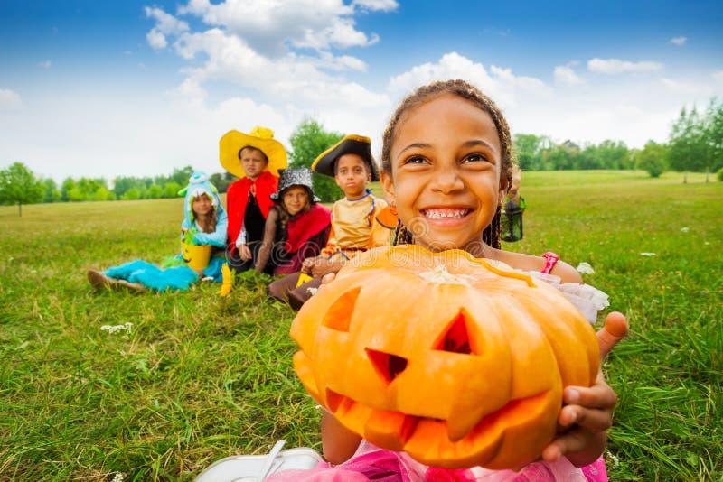 Het gelukkige Afrikaanse meisje houdt Halloween-pompoen stock fotografie