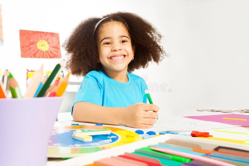 Het gelukkige Afrikaanse meisje houdt potlood het schrijven brieven royalty-vrije stock foto