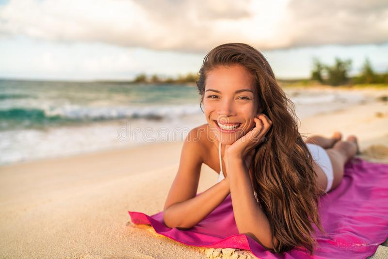 Het gelukkige Aziatische bikini wwoman model ontspannen op de zomervakantie die op strandhanddoek liggen, Hawaï stock afbeeldingen