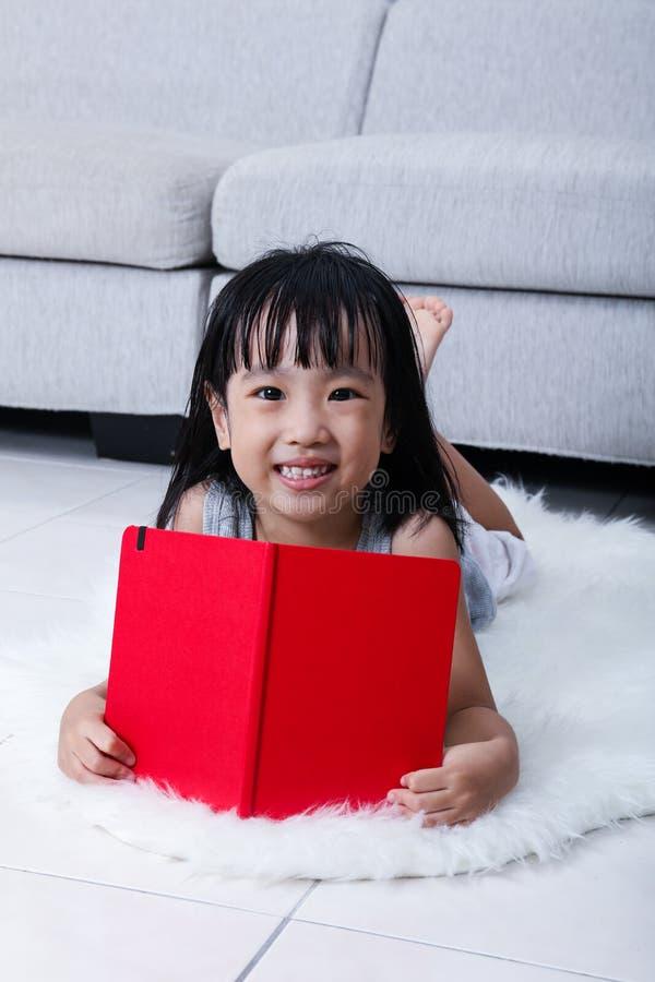Het gelukkige Aziatische Chinese boek van de meisjelezing op de vloer stock foto's