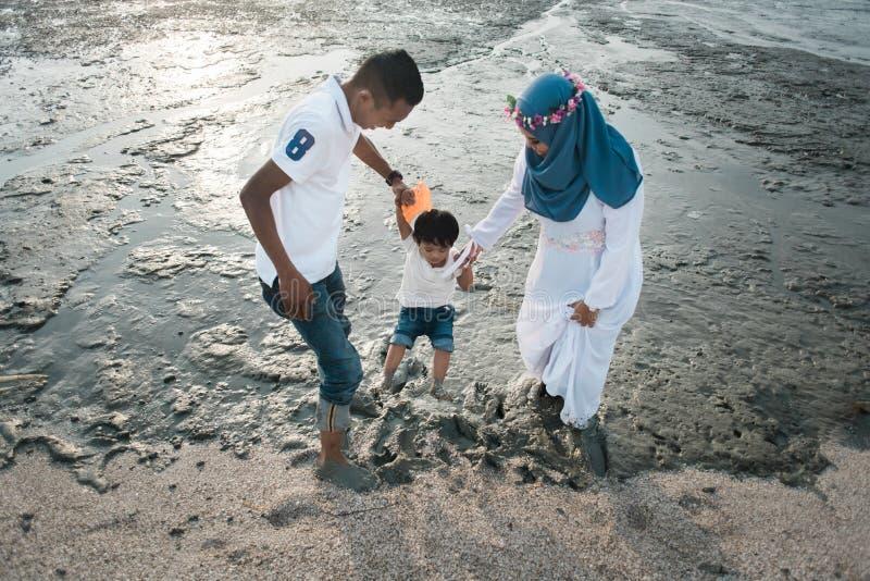 Het gelukkige Aziatische familie dragen toevallig en het spelen met modder bij het modderige strand stock afbeelding