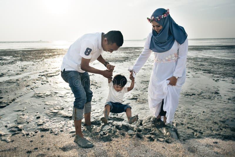 Het gelukkige Aziatische familie dragen toevallig en het spelen met modder bij het modderige strand stock foto's