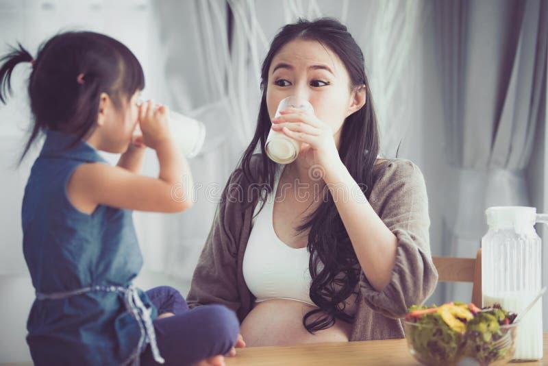Het gelukkige Aziatische familiemamma en de dochter drinken melk royalty-vrije stock foto's