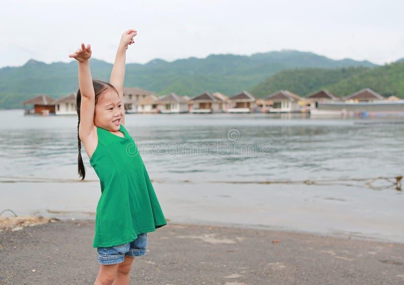 Het gelukkige Aziatische kindmeisje opende haar handen en ontspant in helling royalty-vrije stock foto's