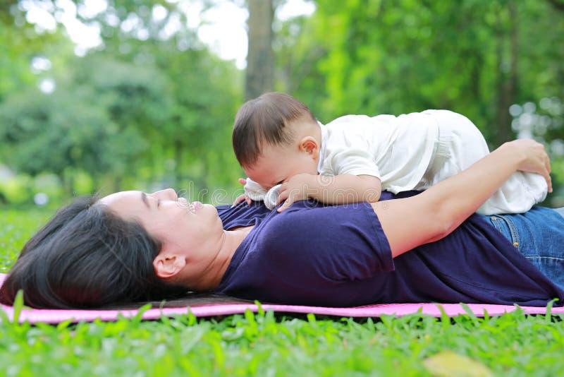 Het gelukkige Aziatische mamma omhelst haar zoon liggend in de groene tuin Het grappige moeder en zuigelingsbabyjongen spelen in  stock foto's