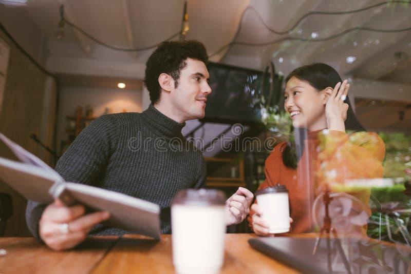 Het gelukkige Aziatische meisje en vrienden babbelen die bij de koffie van de koffiewinkel op universiteit spreken houdt oogconta royalty-vrije stock foto's