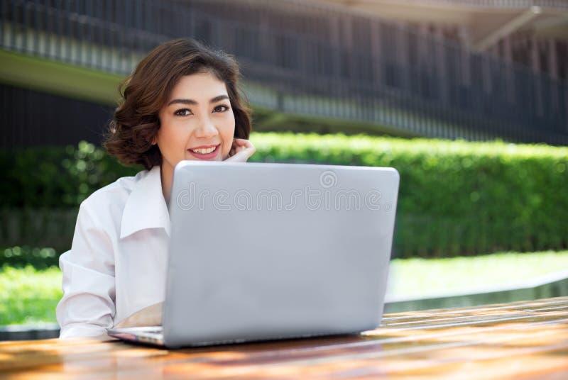 Het gelukkige Aziatische meisje lachen en het richten op laptop het scherm overtreffen  royalty-vrije stock foto