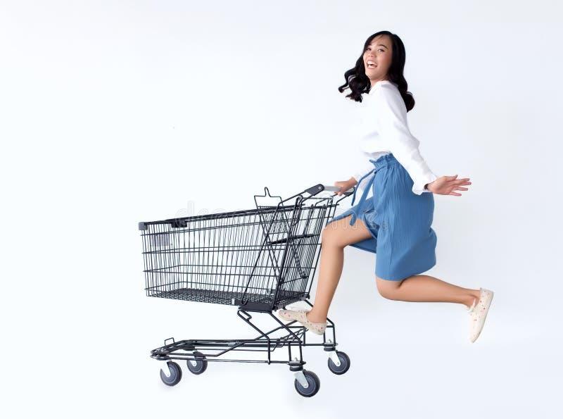 Het gelukkige Aziatische meisje loveshopping met boodschappenwagentje stock afbeeldingen