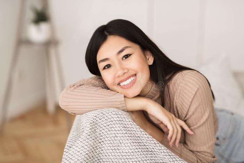 Het gelukkige Aziatische Meisje Ontspannen in Woonkamer royalty-vrije stock fotografie