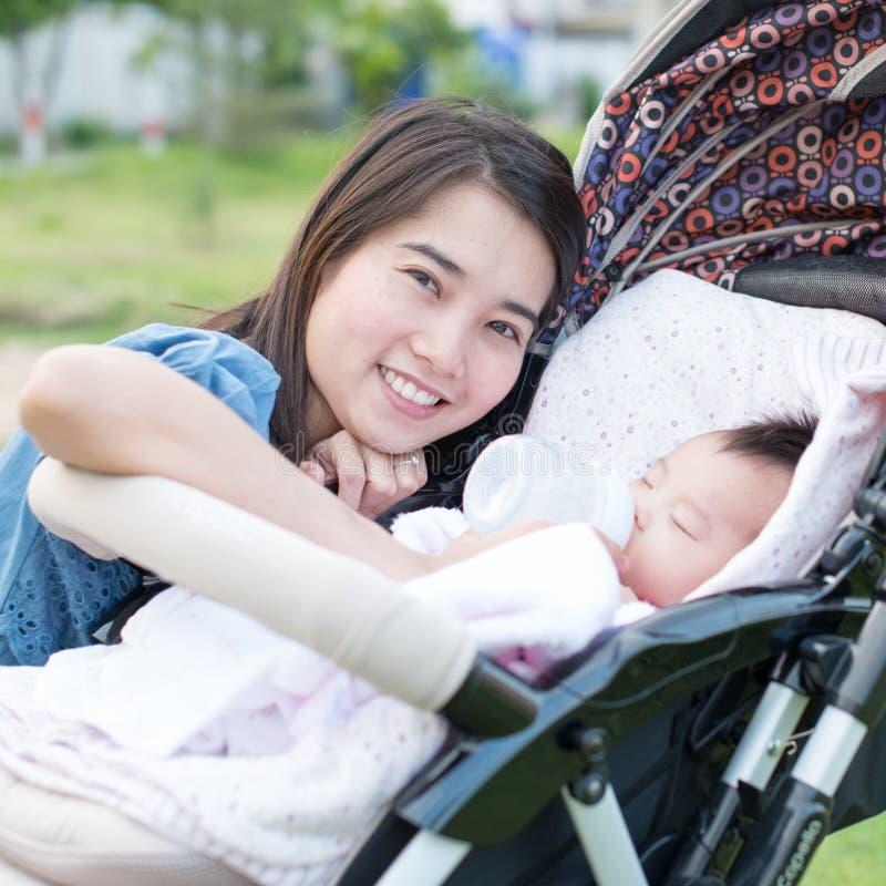 Het gelukkige Aziatische moeder voeden aan baby op de wandelwagen stock foto