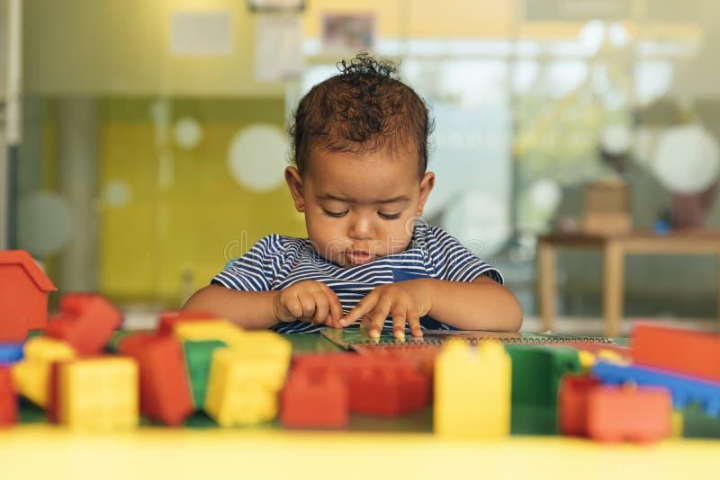 Het gelukkige baby spelen met stuk speelgoed blokken stock afbeeldingen