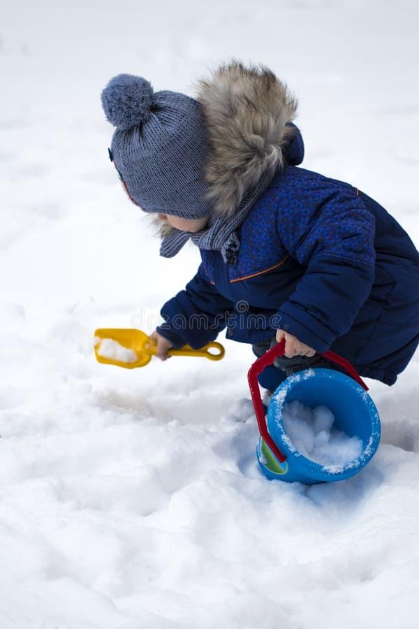 Het gelukkige babyjongen spelen in de sneeuw royalty-vrije stock afbeelding