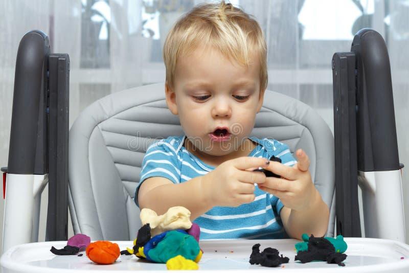 Het gelukkige babyjongen spelen met plasticine Een twee-jaar-oude peuter zit in de babystoel en moldes iets met een klei stock afbeeldingen