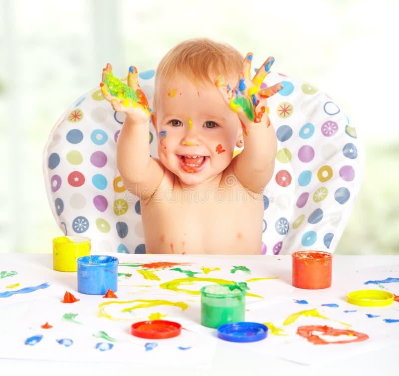Het gelukkige babykind trekt met gekleurde verven royalty-vrije stock fotografie