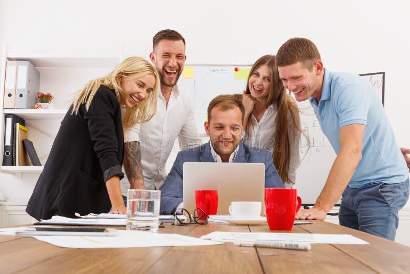 Het gelukkige bedrijfsmensenteam heeft samen pret in bureau stock afbeeldingen