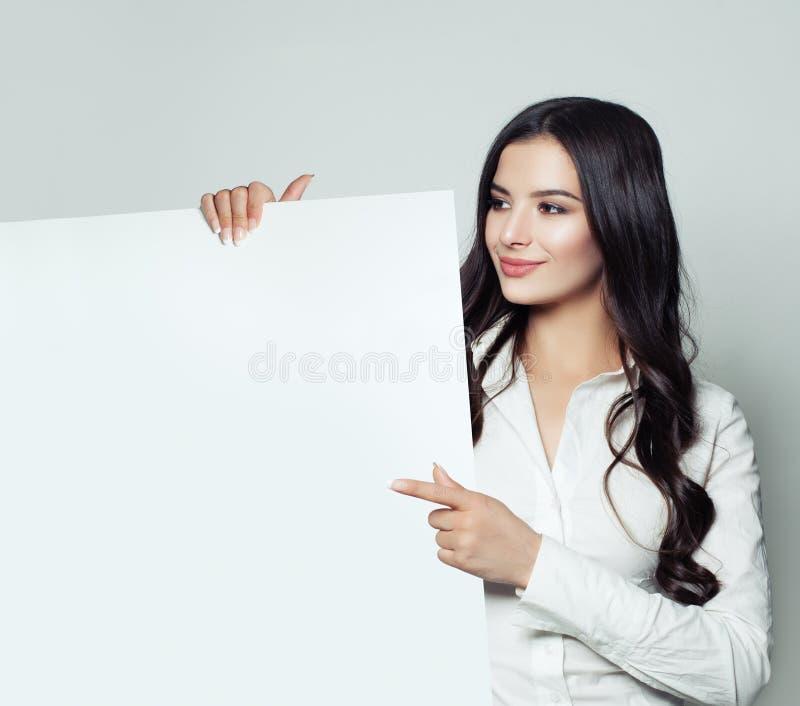 Het gelukkige bedrijfsvrouw donkerbruine glimlachen, die wit leeg document tonen royalty-vrije stock afbeelding