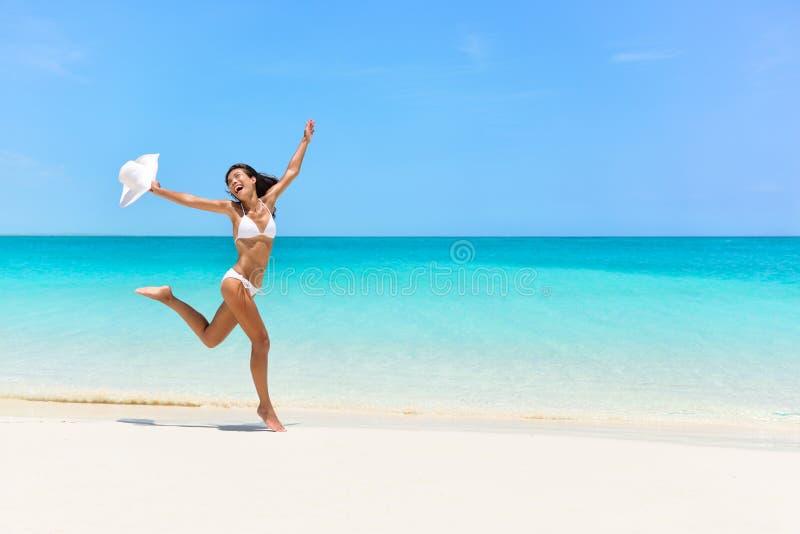 Het gelukkige bikinivrouw springen van vreugde op wit strand stock afbeeldingen