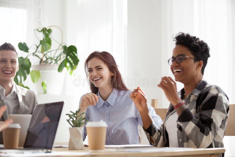 Het gelukkige blije diverse bedrijfsmensen lachen die bij het werkonderbreking spreken stock afbeelding
