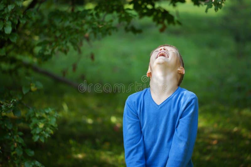 Het gelukkige blije mooi lachen weinig jongen op groene achtergrond royalty-vrije stock afbeelding