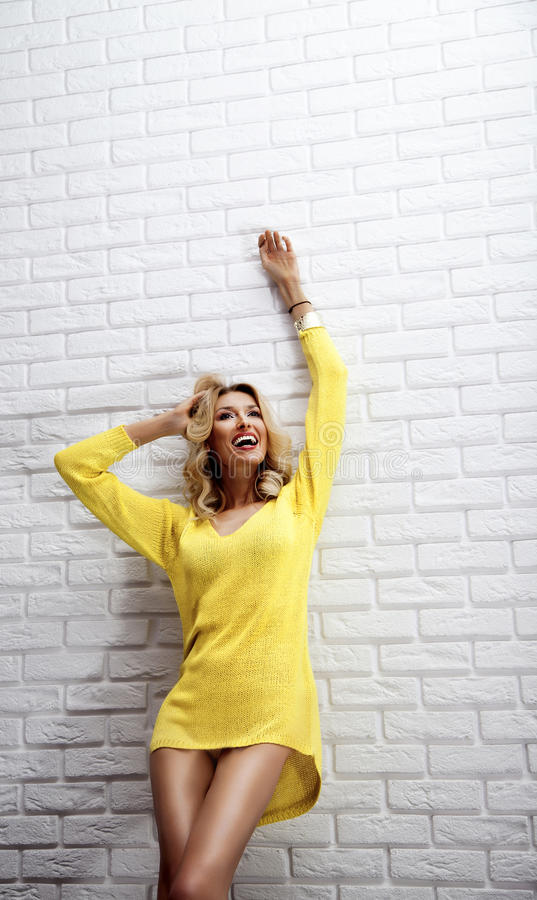 Het gelukkige blondevrouw stellen met toothy glimlach. royalty-vrije stock fotografie