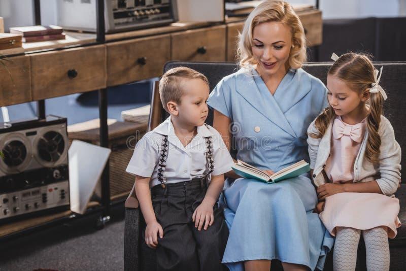 het gelukkige boek van de moederlezing terwijl het zitten met aanbiddelijke kleine jonge geitjes op bank thuis jaren '50 stock afbeeldingen