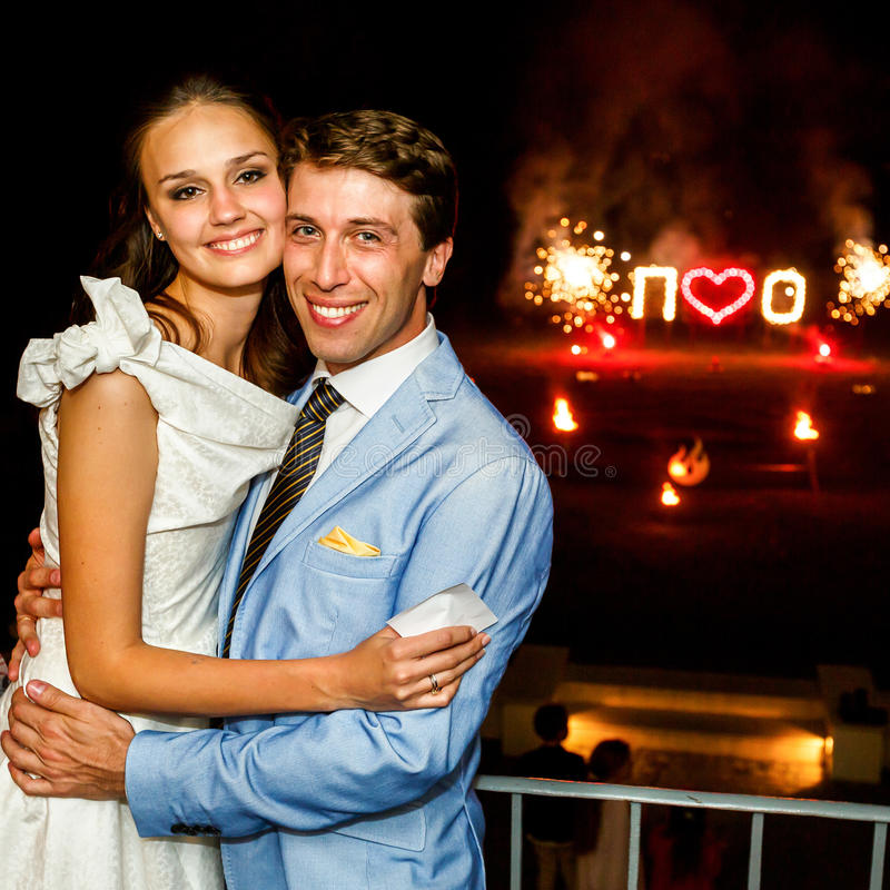 Het gelukkige bruid en bruidegom koesteren die op achtergrondvuurwerk glimlachen stock foto