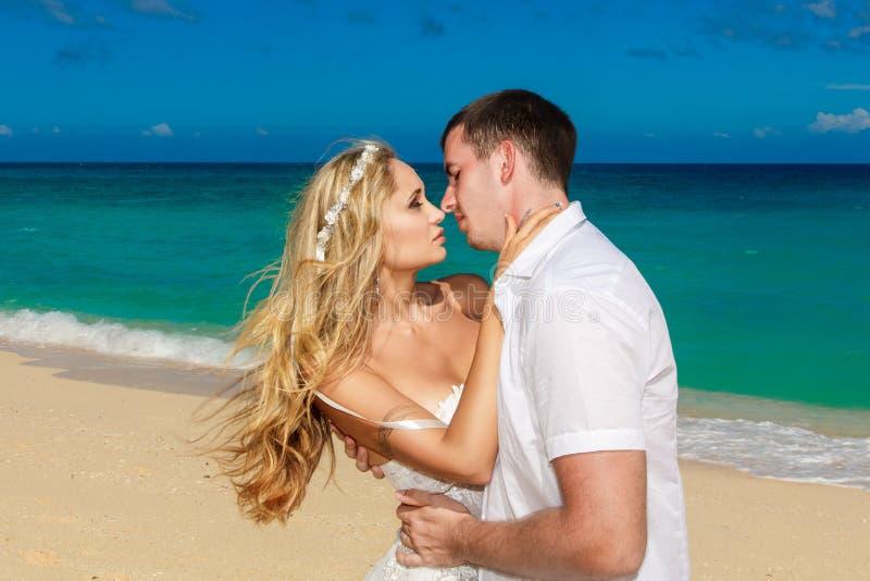 Het gelukkige bruid en bruidegom kussen op een tropisch strand Blauwe overzees in t royalty-vrije stock afbeeldingen