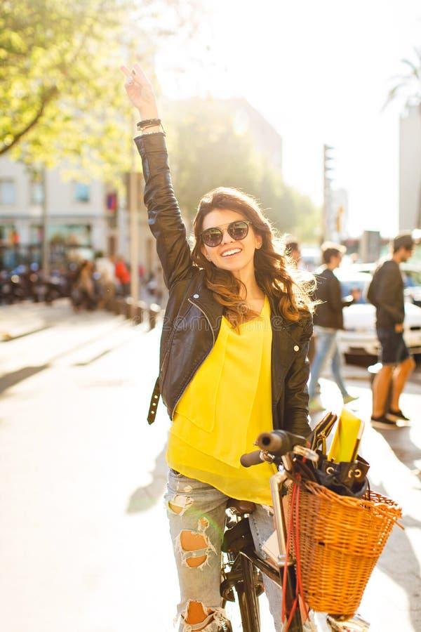 Het gelukkige brunette gir in zonnebril stelt op fiets op zonnige straat in stad Zij draagt geel overhemd, heft haar hand op en stock foto