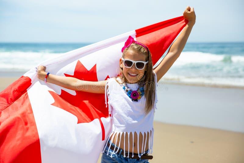 Het gelukkige Canadese meisje draagt fladderende witte rode vlag van Canada tegen blauwe hemel en oceaanachtergrond stock afbeeldingen