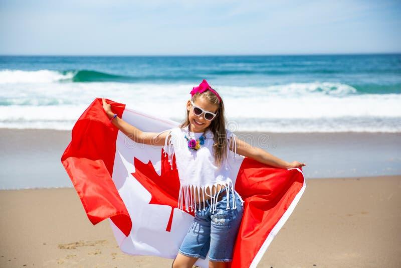 Het gelukkige Canadese meisje draagt fladderende witte rode vlag van Canada tegen blauwe hemel en oceaanachtergrond royalty-vrije stock fotografie