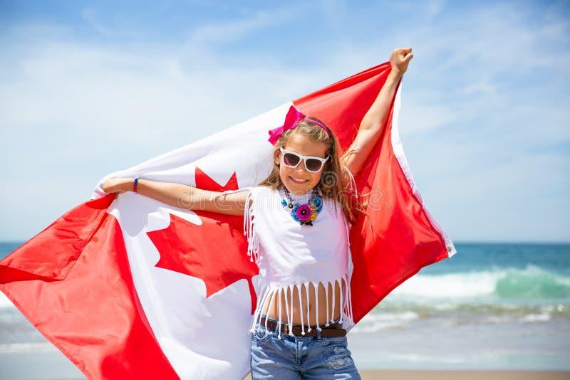 Het gelukkige Canadese meisje draagt fladderende witte rode vlag van Canada tegen blauwe hemel en oceaanachtergrond royalty-vrije stock foto