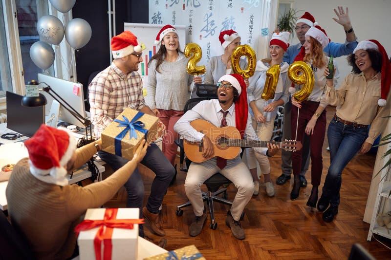 Het gelukkige commerciële team heeft pret en samen het dansen in Kerstmanhoed bij Kerstmispartij royalty-vrije stock foto's