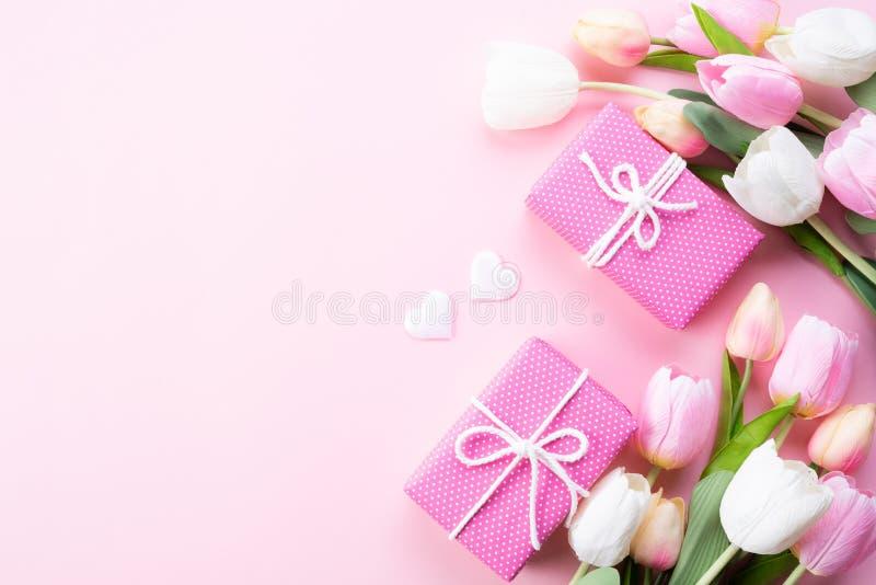 Het gelukkige concept van de moedersdag De hoogste mening van roze tulp bloeit, giftdoos op roze pastelkleurachtergrond Vlak leg royalty-vrije stock foto's