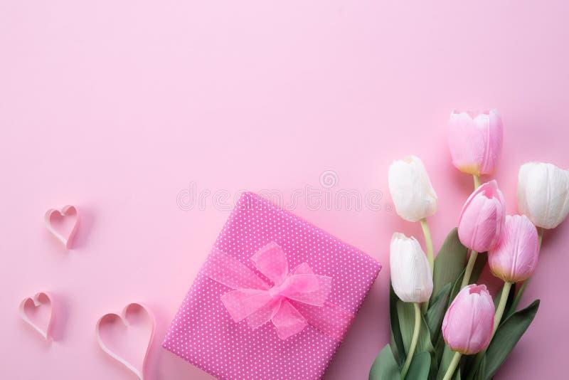 Het gelukkige concept van de moedersdag De hoogste mening van roze tulp bloeit, giftvakje en document hart op roze pastelkleurach stock afbeelding