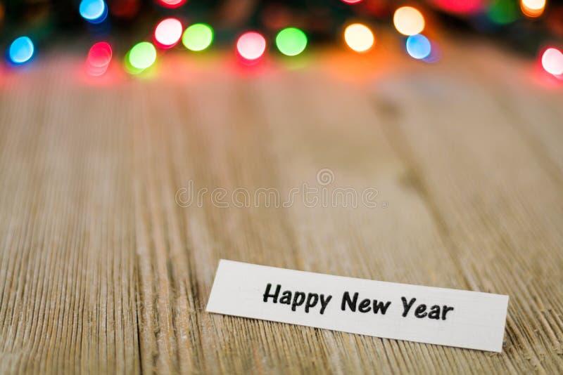Het gelukkige Concept van de Nieuwjaarverkoop op houten raad en gekleurde lichten, selectieve nadruk, ruimte voor exemplaar stock fotografie