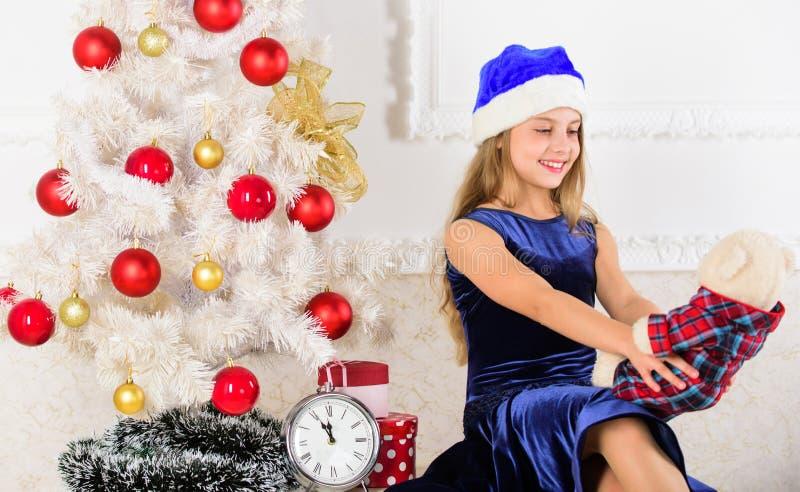 Het gelukkige Concept van het Nieuwjaar Het jonge geitje zit dichtbij de gift van de de greepteddybeer van de Kerstmisboom Opwind stock afbeelding