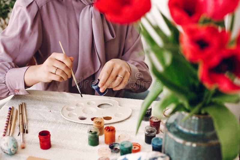 Het gelukkige concept van Pasen handen die en paaseieren houden schilderen royalty-vrije stock afbeeldingen