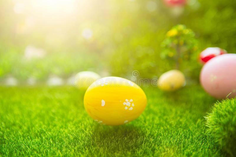 Het gelukkige concept van Pasen Kleurrijke paaseieren en één groot geel paasei op de lente groen gras Sprookjezonsondergang op pl stock fotografie