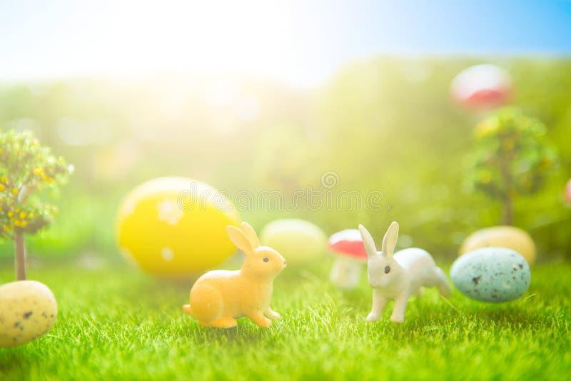 Het gelukkige concept van Pasen Pasen-konijnenstuk speelgoed op de lente groen gras Sprookjezonsondergang op het plastic groene g royalty-vrije stock foto's