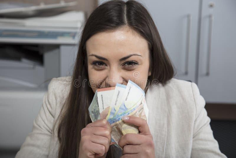 Het gelukkige contante geld van de bedrijfsvrouwenholding in handen royalty-vrije stock afbeeldingen