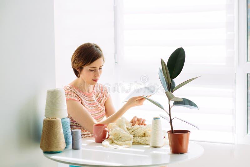 Het gelukkige craftswoman bekijken in tablet steekproef terwijl de breiende kleding met in comfortabel werkplaats thuis binnenlan stock afbeelding