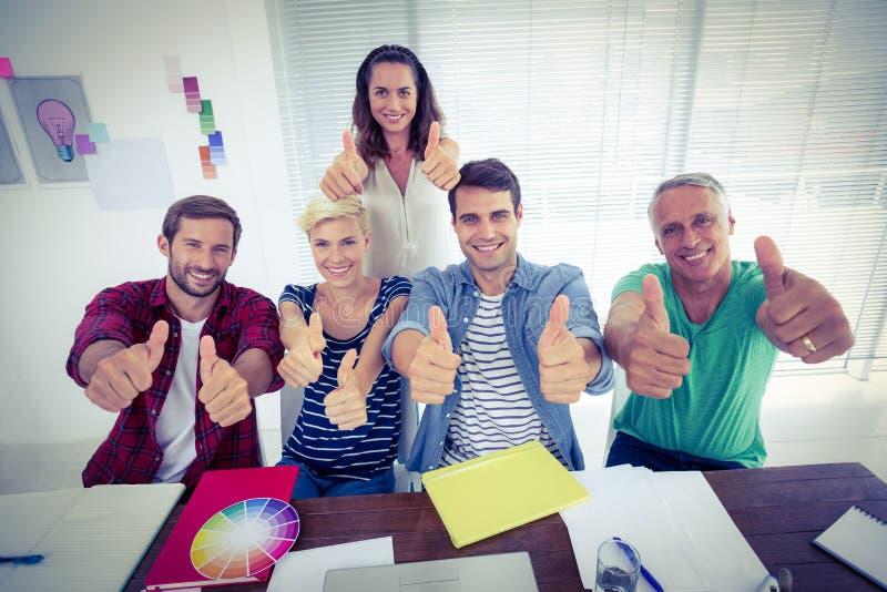 Het gelukkige creatieve commerciële team gesturing beduimelt omhoog stock fotografie