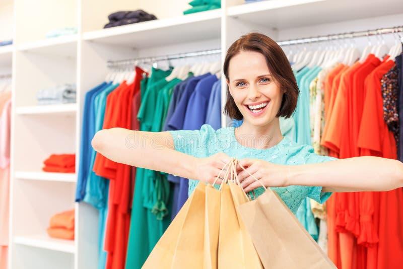 Het gelukkige dame opscheppen van aankoop in winkel stock afbeeldingen
