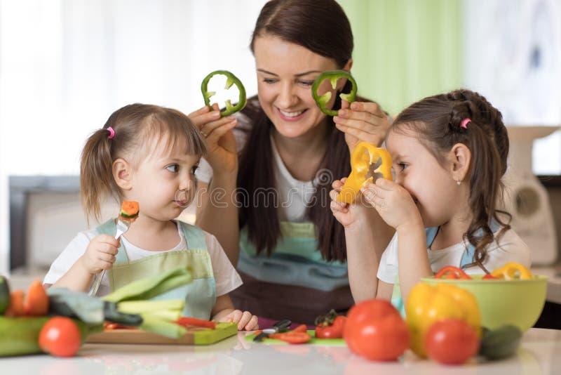 Het gelukkige de familiemamma en jonge geitjes die pret met voedselgroenten hebben bij keuken houden peper vóór hun ogen als in g royalty-vrije stock foto's